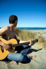 James with guitar on beach